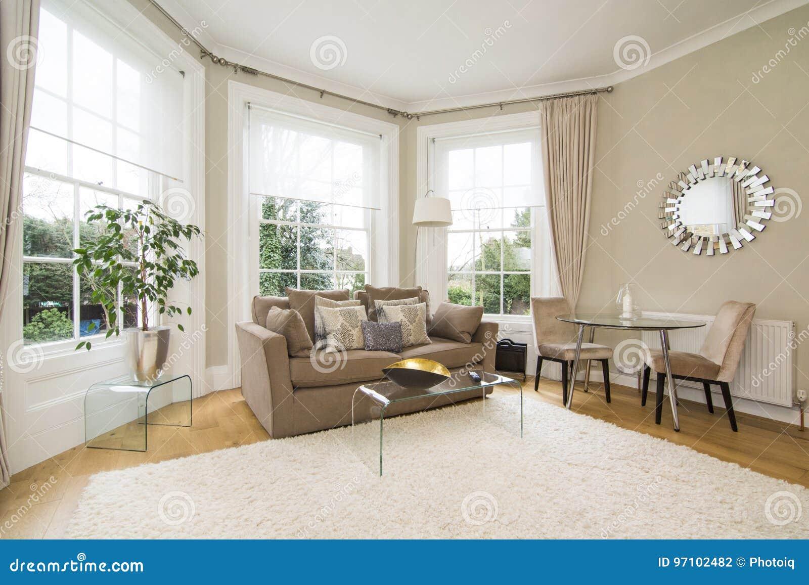 Klassieke woonkamer met grote erker die mooie tuin onder ogen zien