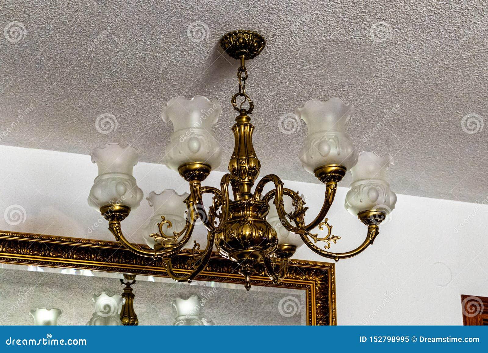 Klassisk ljuskrona från det vita taket med spegeln och vita väggar