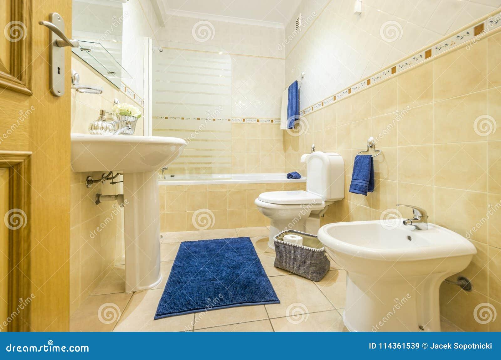Klassiskt badrum med den blåa handdukar och filten