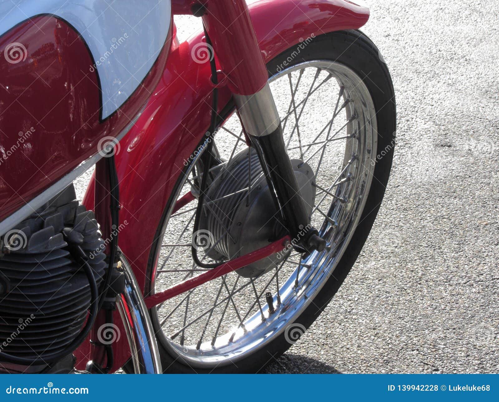 Klassiskt motorcykelanseende på vägen Closeup av mopedframhjulet