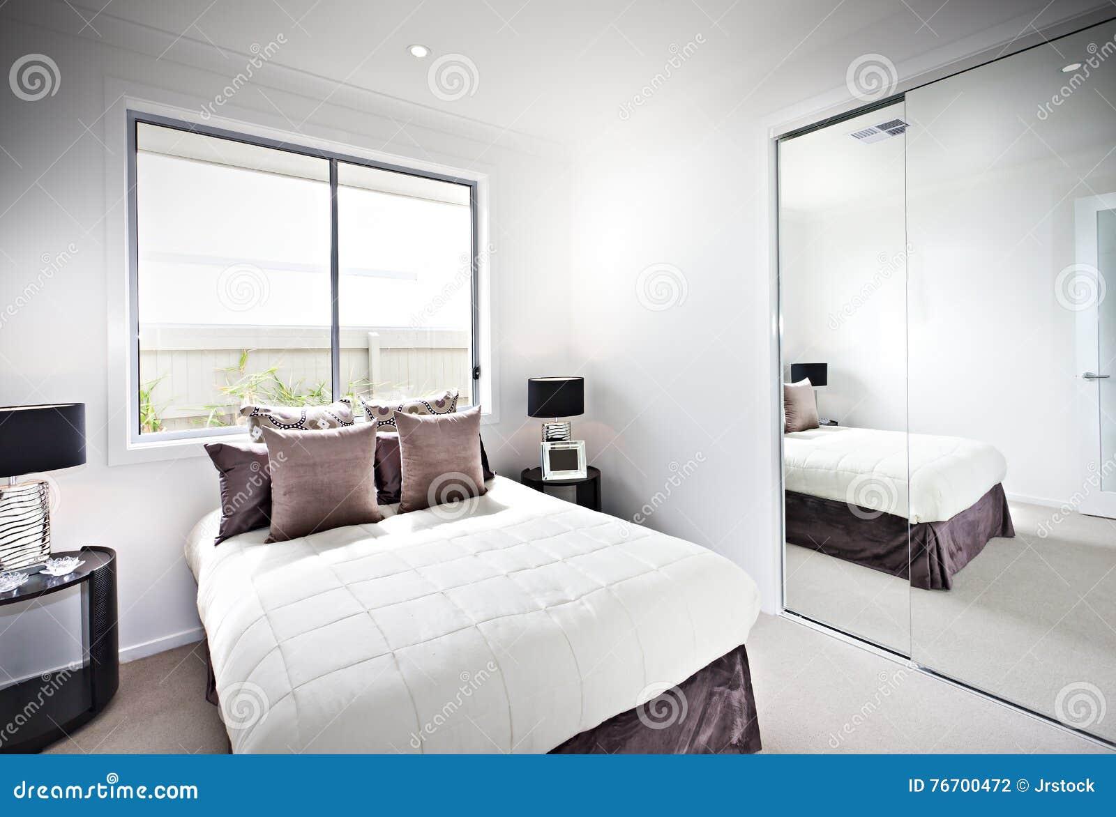 Klassiskt sovrum med fönster och lampor bredvid en spegel