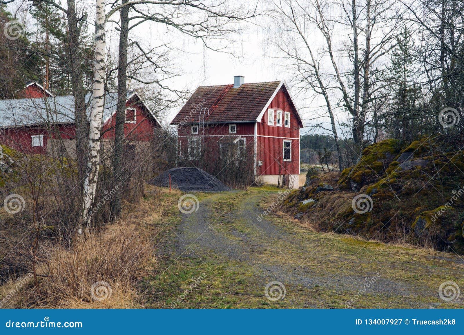 Klassiskt traditionellt rött trähus i Skandinavien bygd, Finland