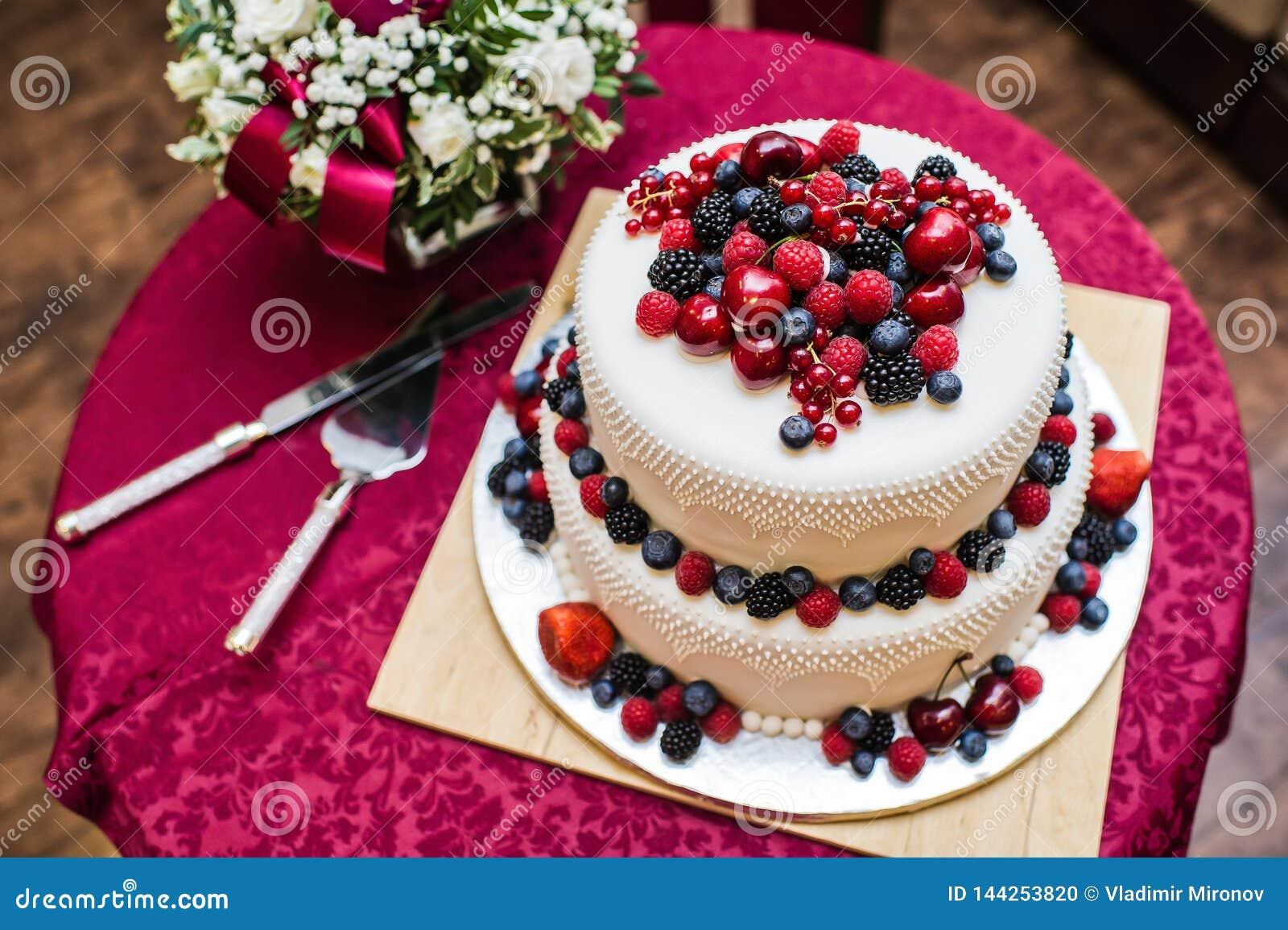 Klasyczny ślubny tort z malinkami, truskawkami, czernicami i blueberrie,