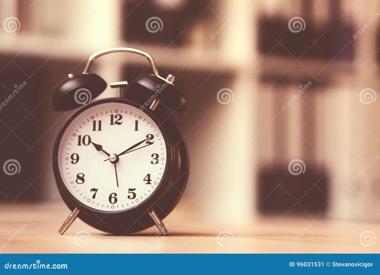 Klasyczny budzik pokazuje czas podczas godzin pracujących w biurze