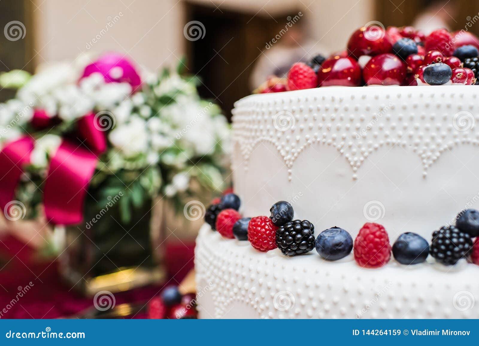 Klasyczny ?lubny tort z malinkami, truskawkami, czernicami i czarnymi jagodami,