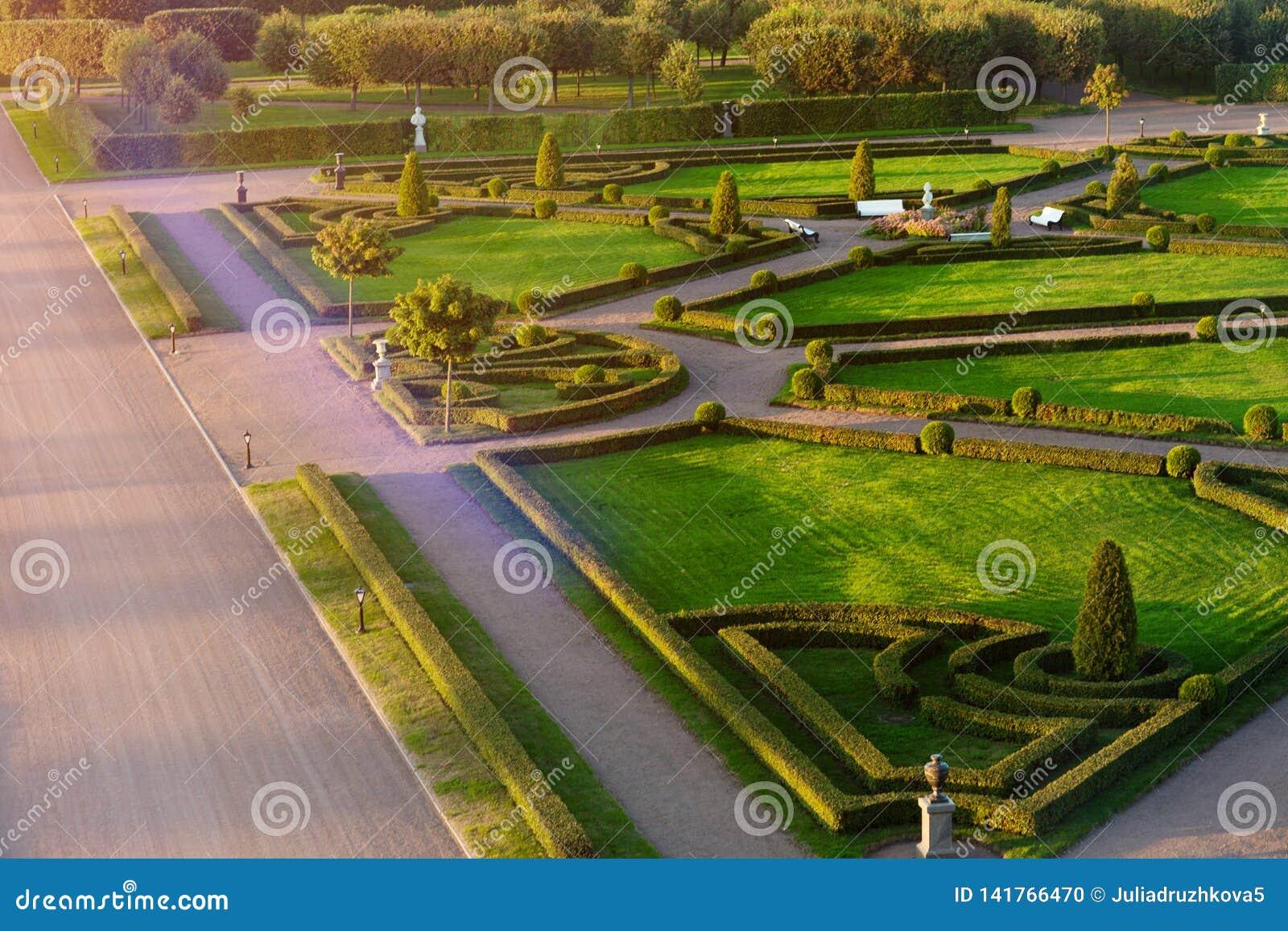 Klasyka park z alejami, rzeźbami i zielonym labiryntem,