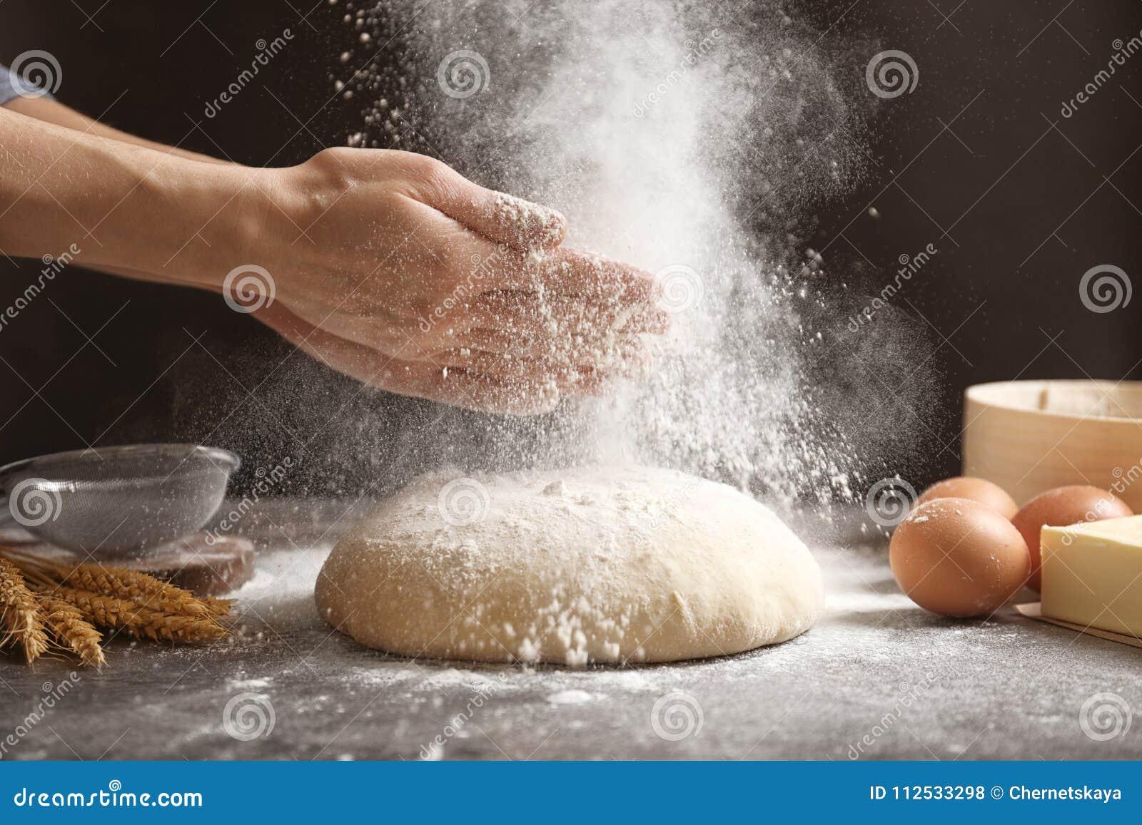 Klatschende Hände der Frau und besprühen Mehl