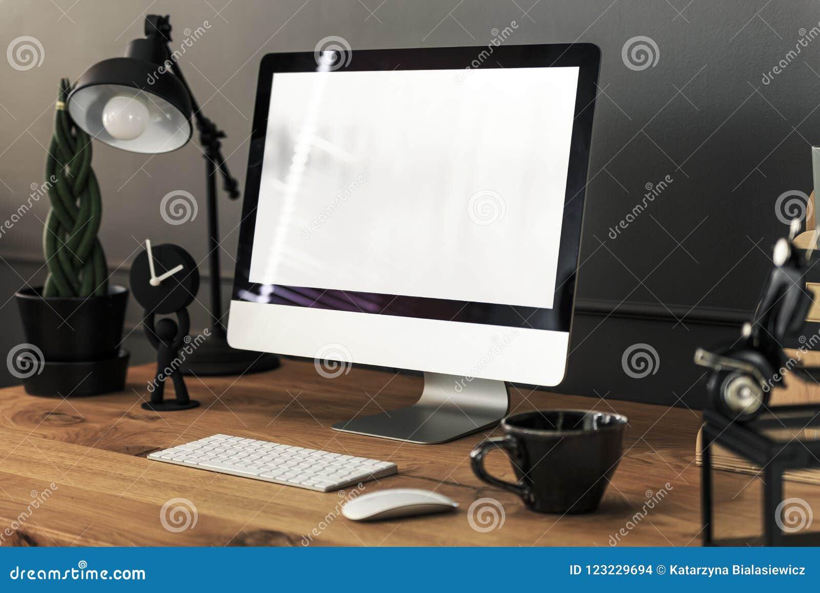Klawiatura, mysz i komputer stacjonarny na drewnianym biurku z lampą wewnątrz,