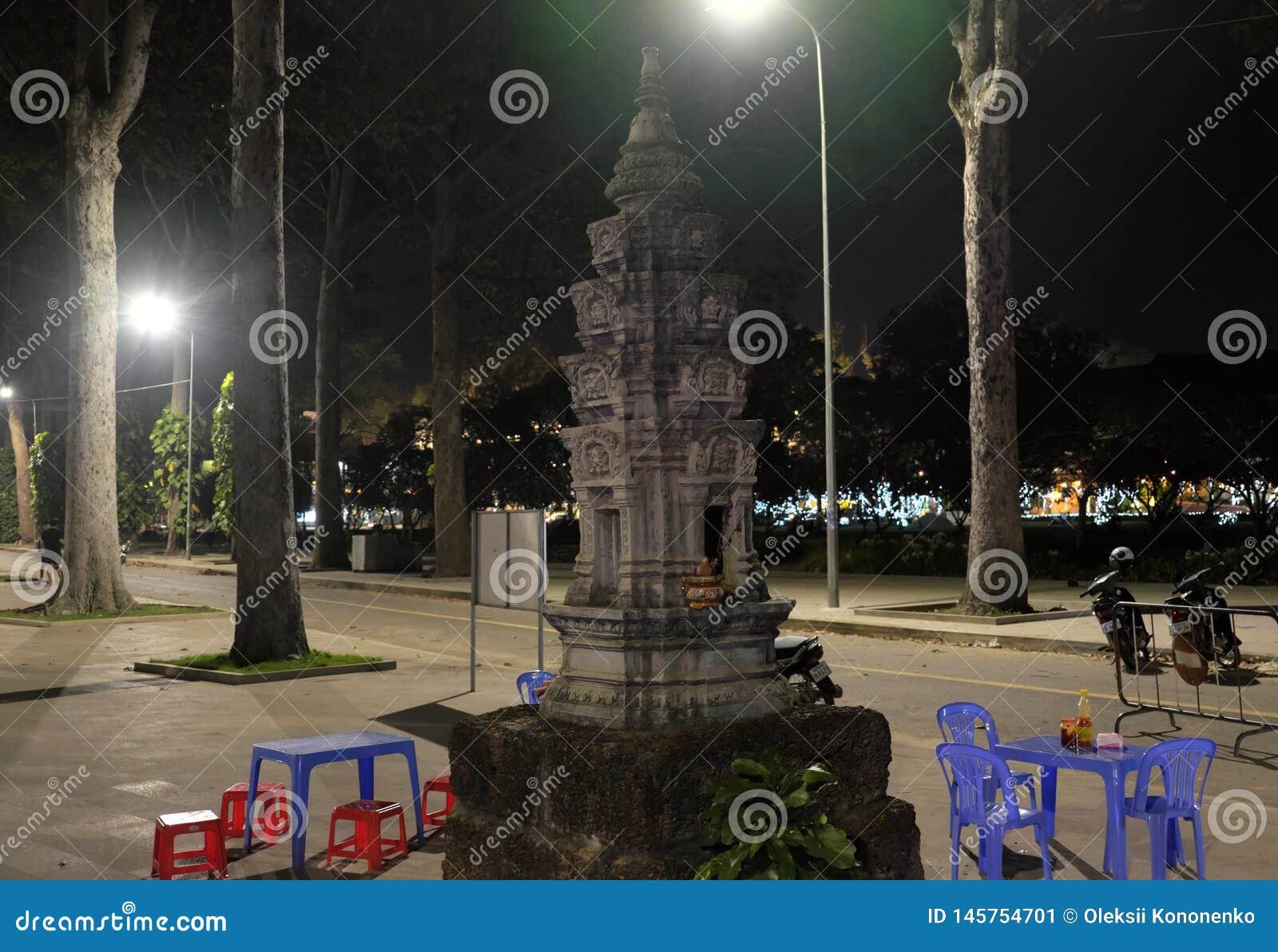 Klein Boeddhistisch altaar in het park Een lijst en verscheidene plastic stoelen Lantaarnlicht
