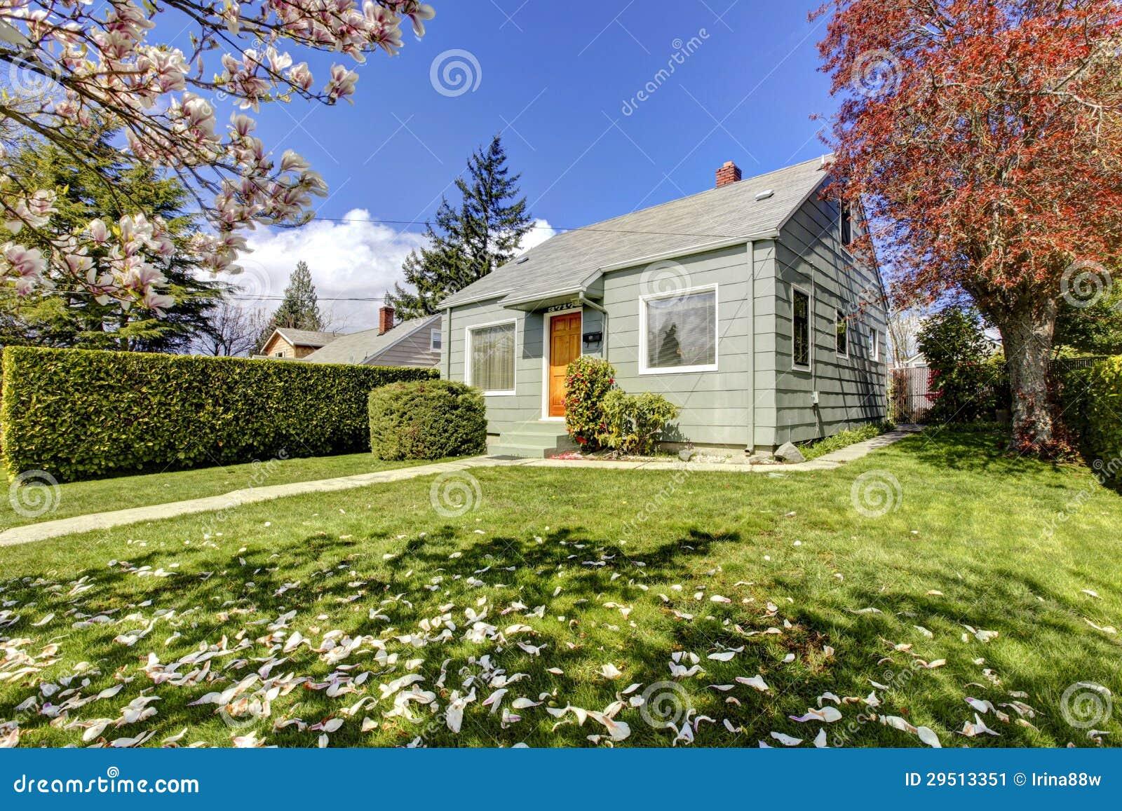 Klein groen huis buiten met de lente bloeiende bomen.