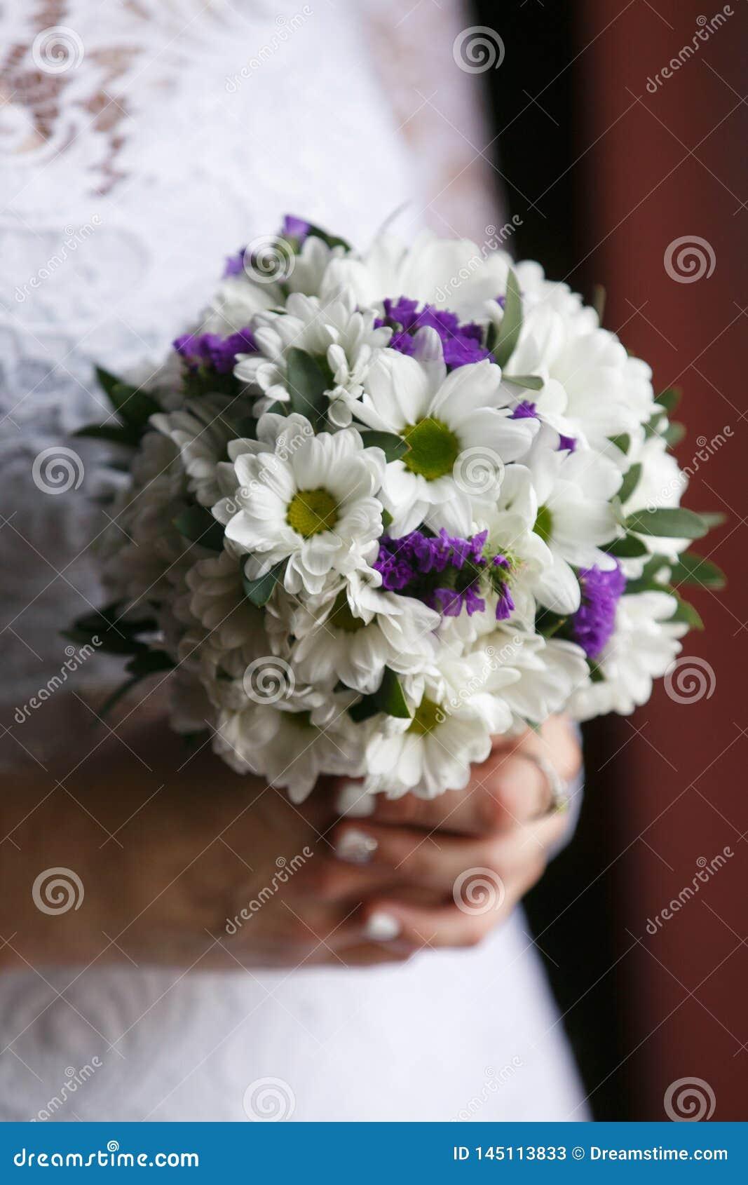 Klein huwelijksboeket in de handen van de bruid