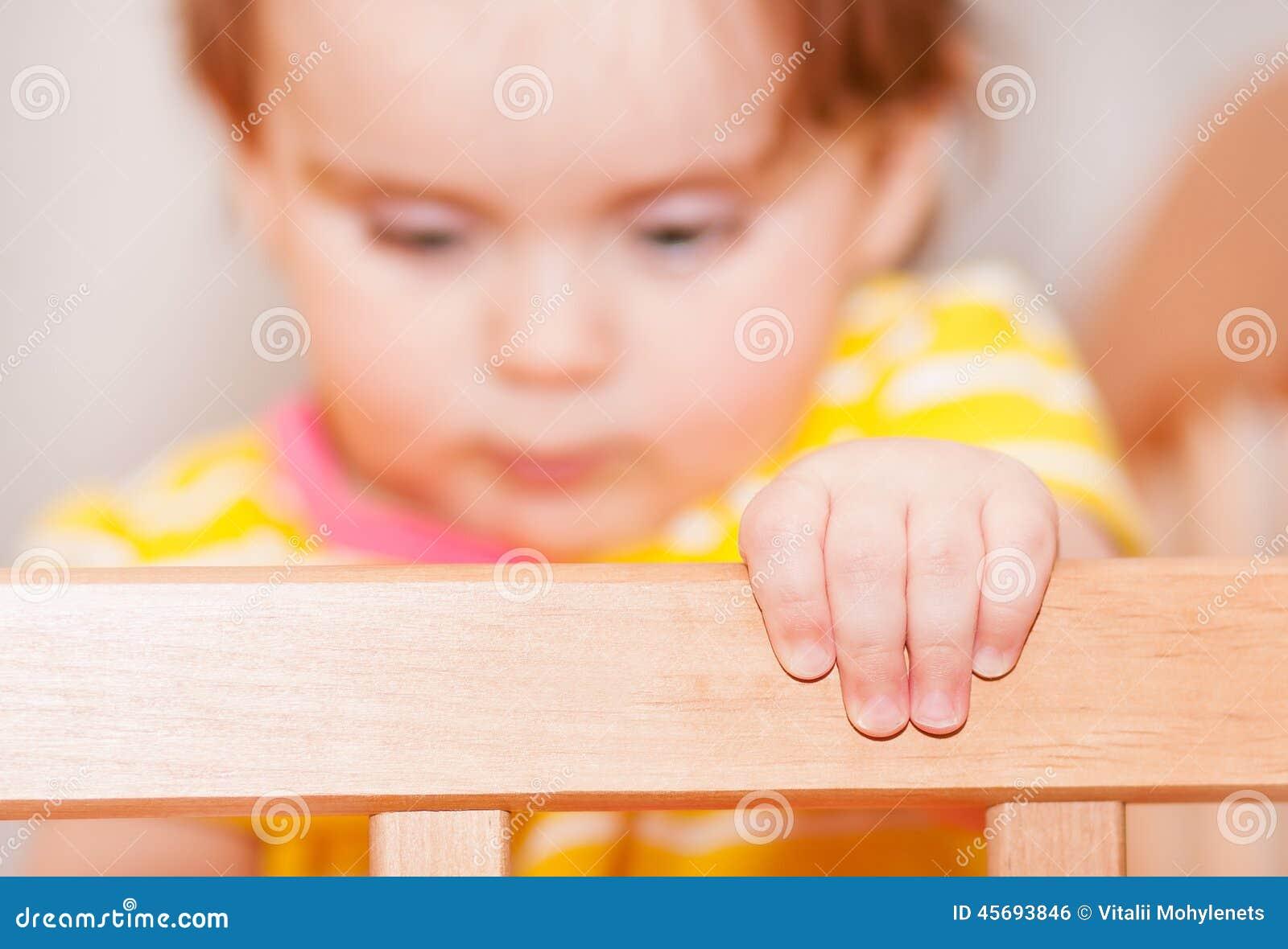 Klein kind met een haarspeld die zich in voederbak bevindt Vage achtergrond