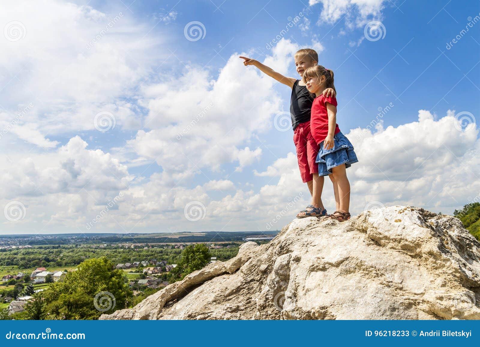 Klein kinderenjongen en meisje die zich op bergrots en looki bevinden