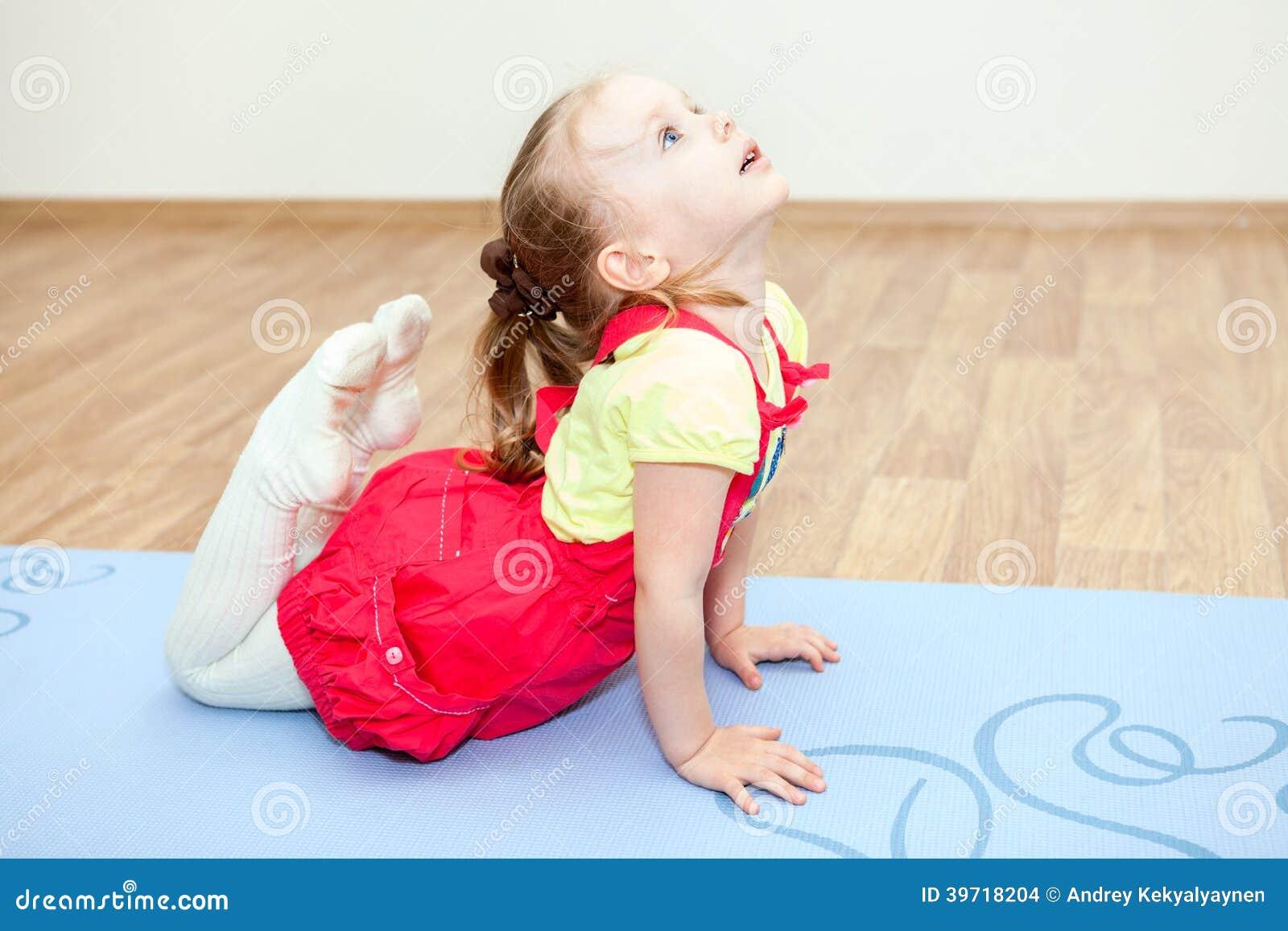 Klein meisje die yoga maken op mat in gymnastiek stellen