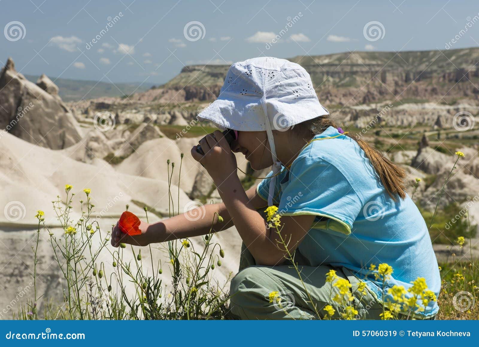 Klein meisje met binoculair in bergen