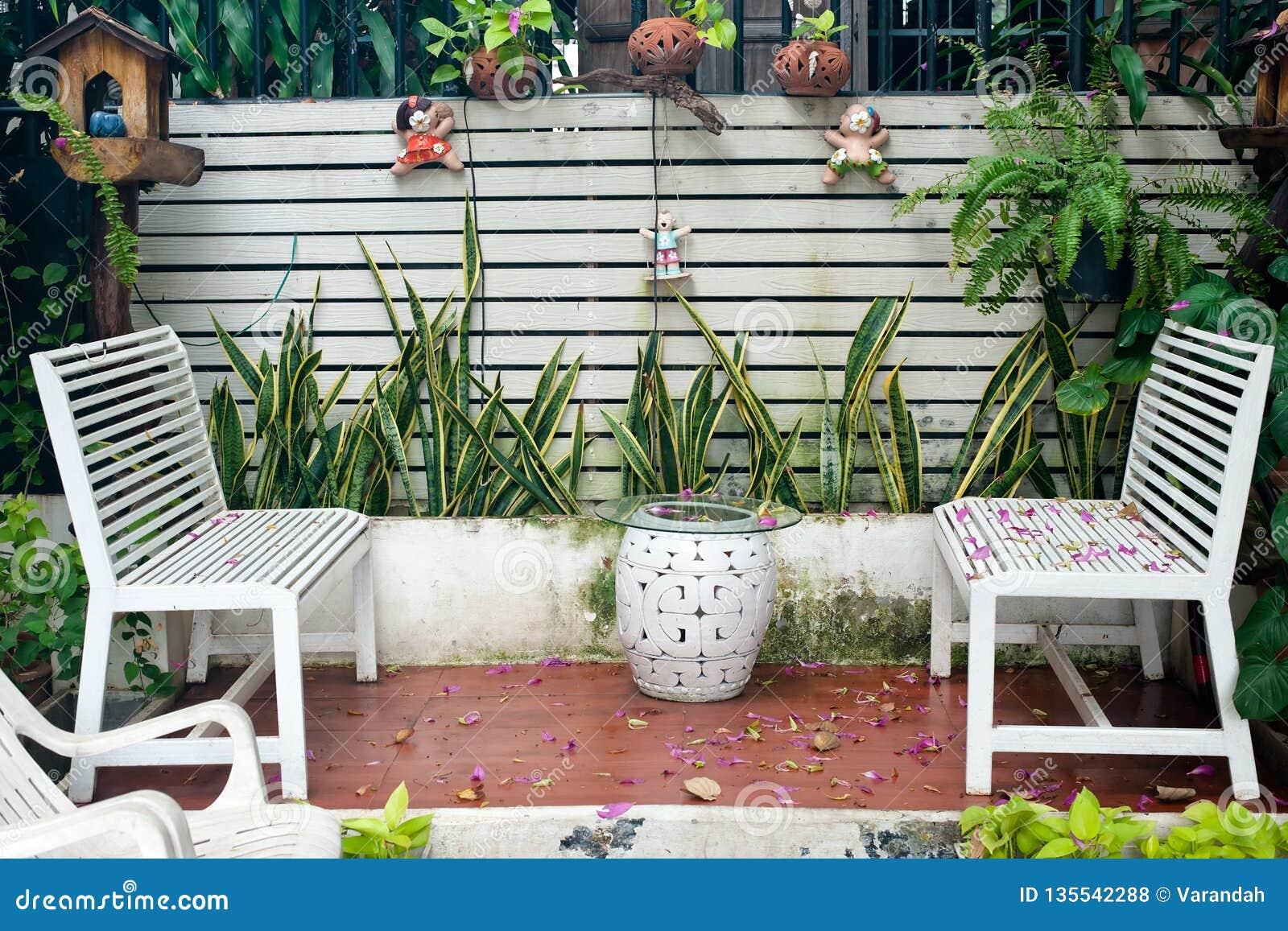 Klein tropisch huisbalkon met groene installaties in potten en witte bank