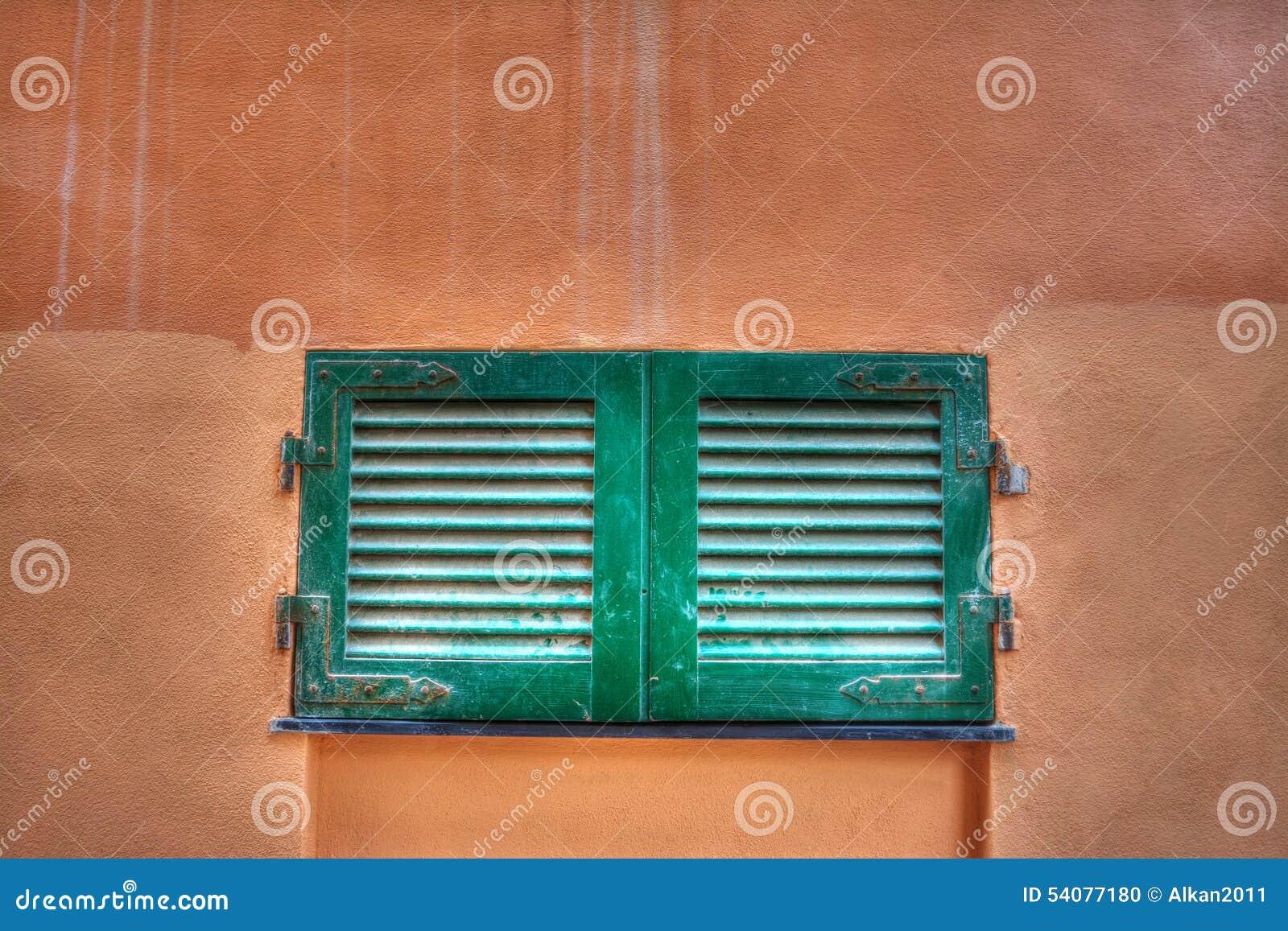 Klein venster in een oranje muur