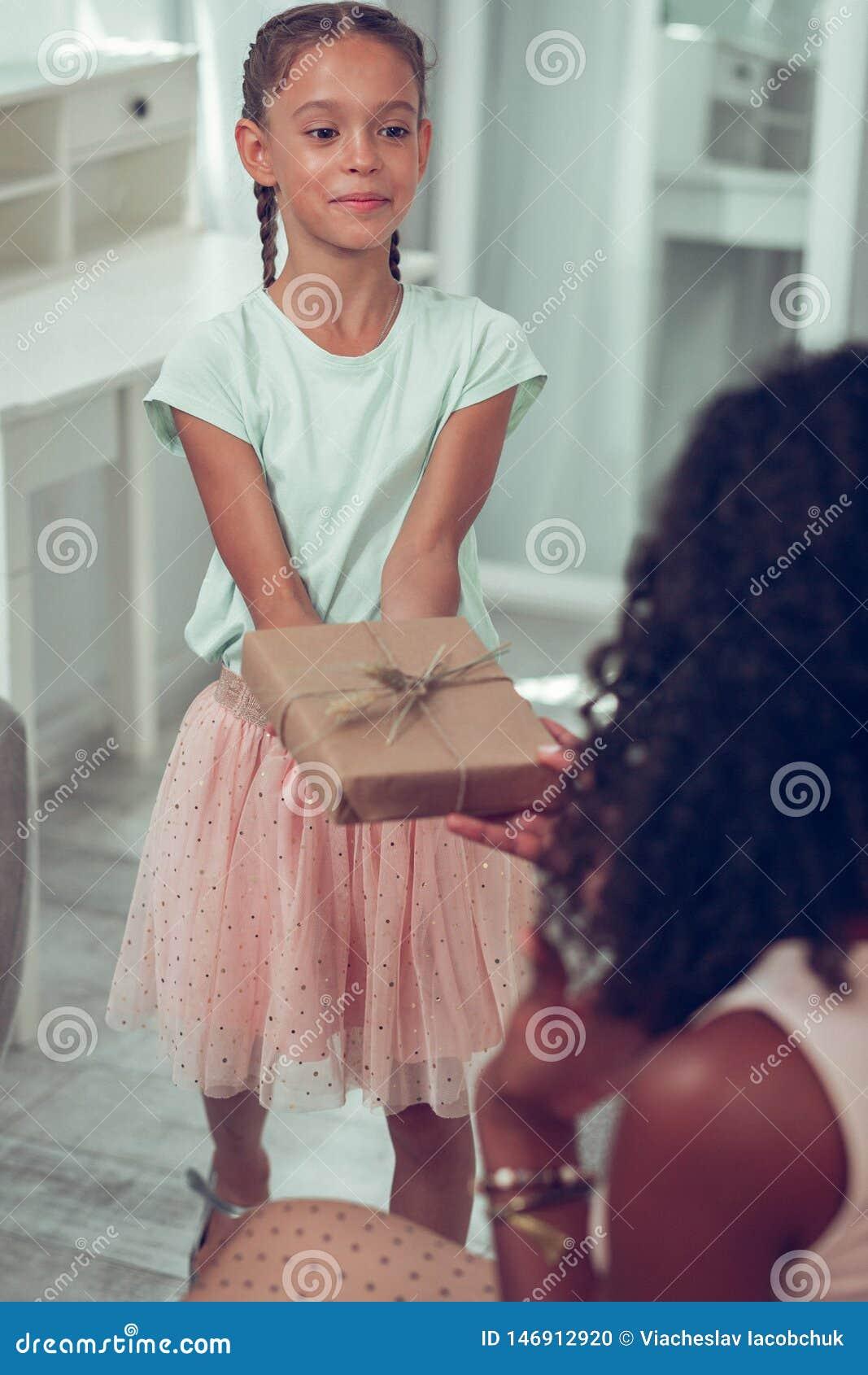 Kleine Afro-Amerikaanse dochter die een gift overhandigen aan een mamma