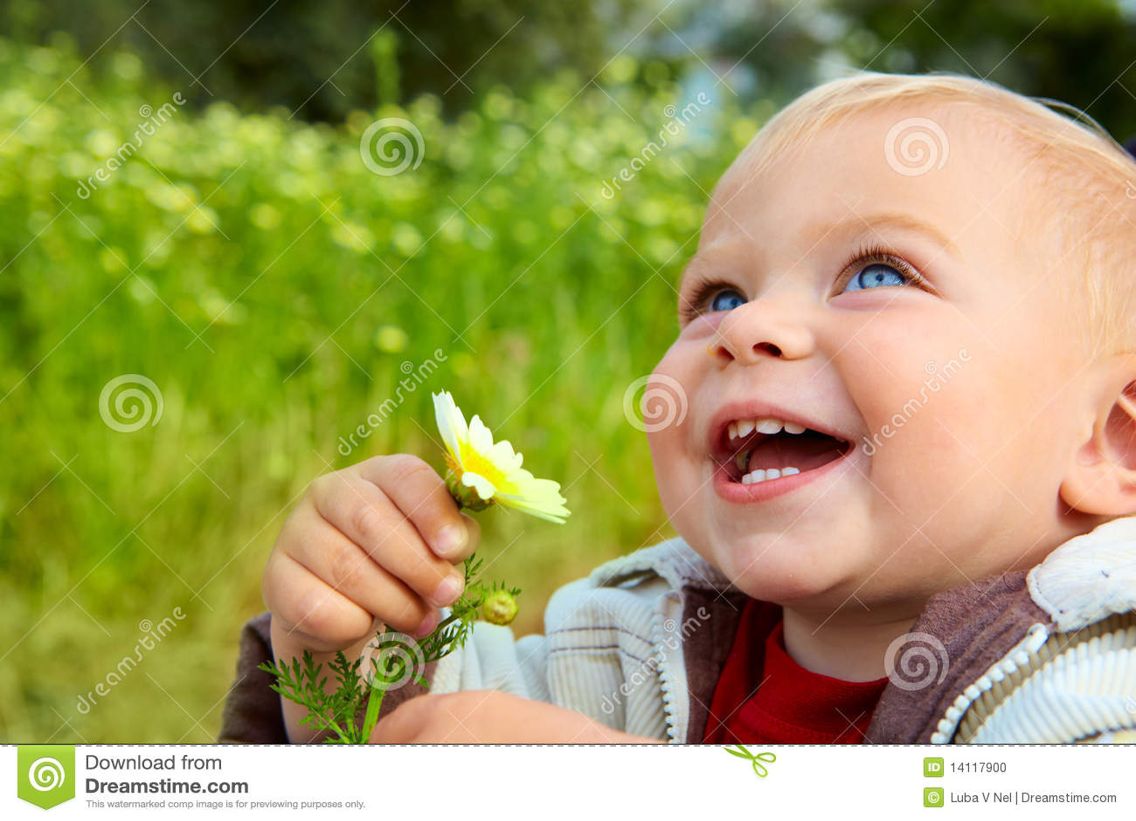 Kleine baby die met madeliefje lacht