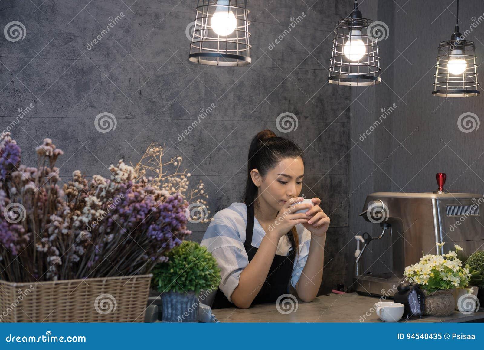 Kleine bedrijfseigenaar bij haar koffiewinkel gelukkige Aziatische vrouwentribune