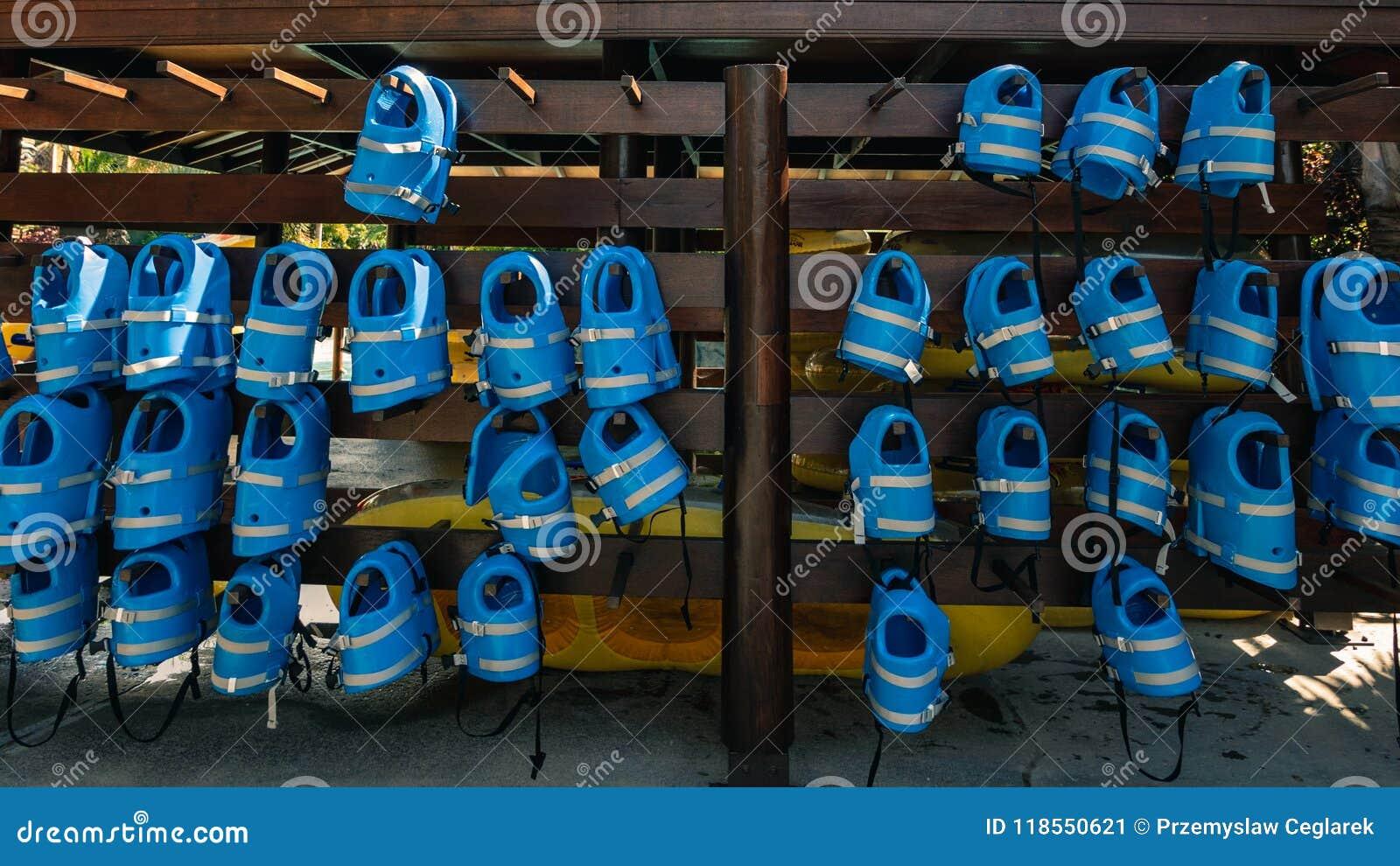 Kleine blaue Schwimmwesten für Kinder hängen in der Reihe am poo