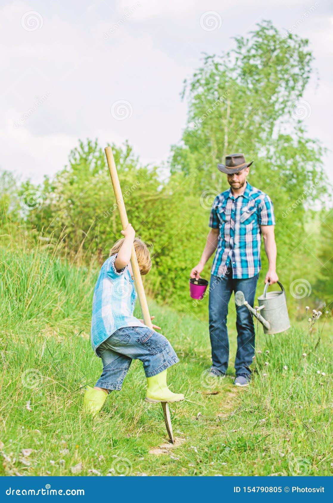 Kleine de hulpvader van het jongenskind in de landbouw Het nieuwe leven gronden en meststoffen vader en zoon die stamboom planten