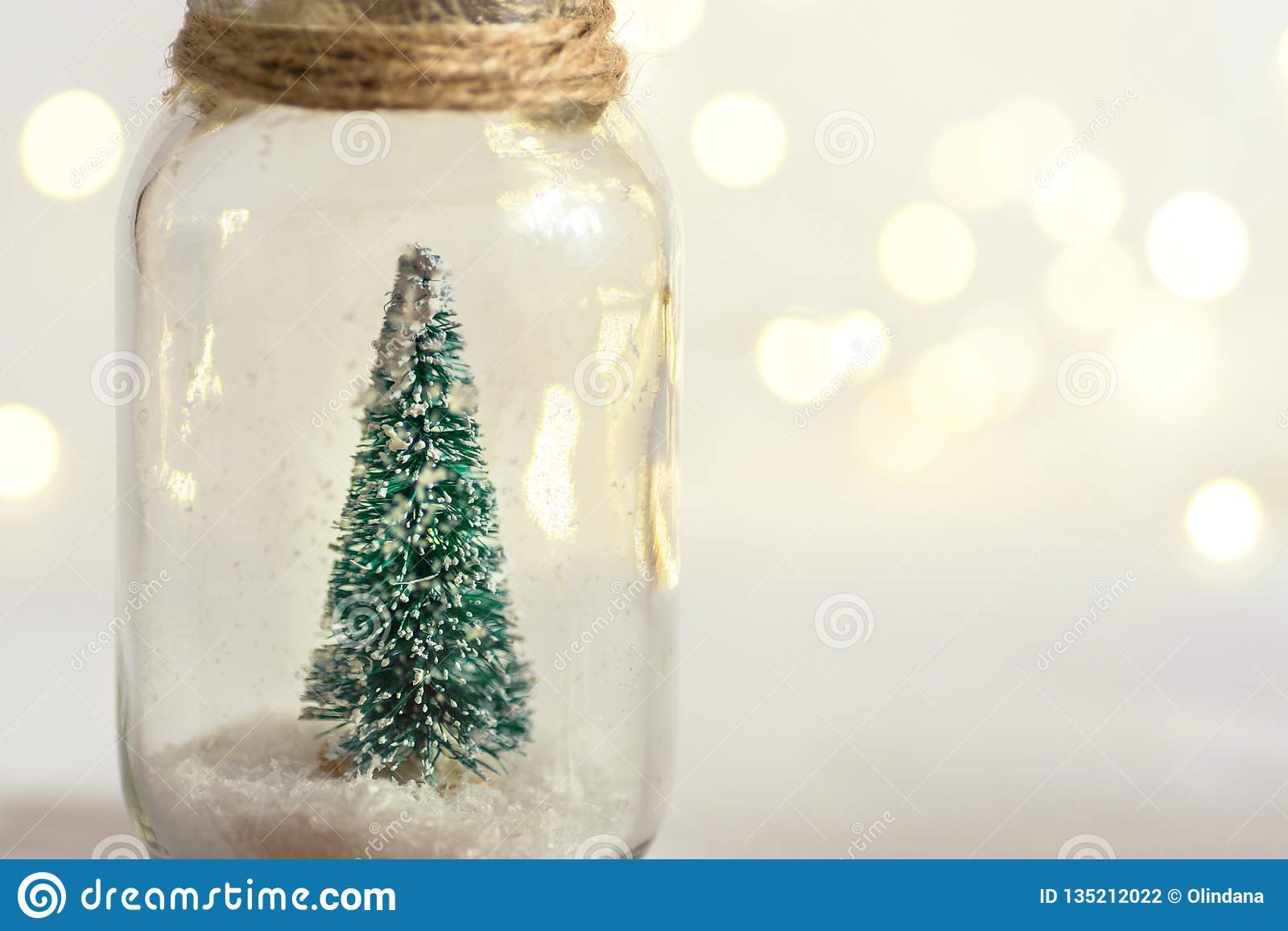 Kleine decoratieve die Kerstboom in glaskruik met streng wordt gebonden Sneeuw gouden slinger bokeh het fonkelen lichten De nieuw