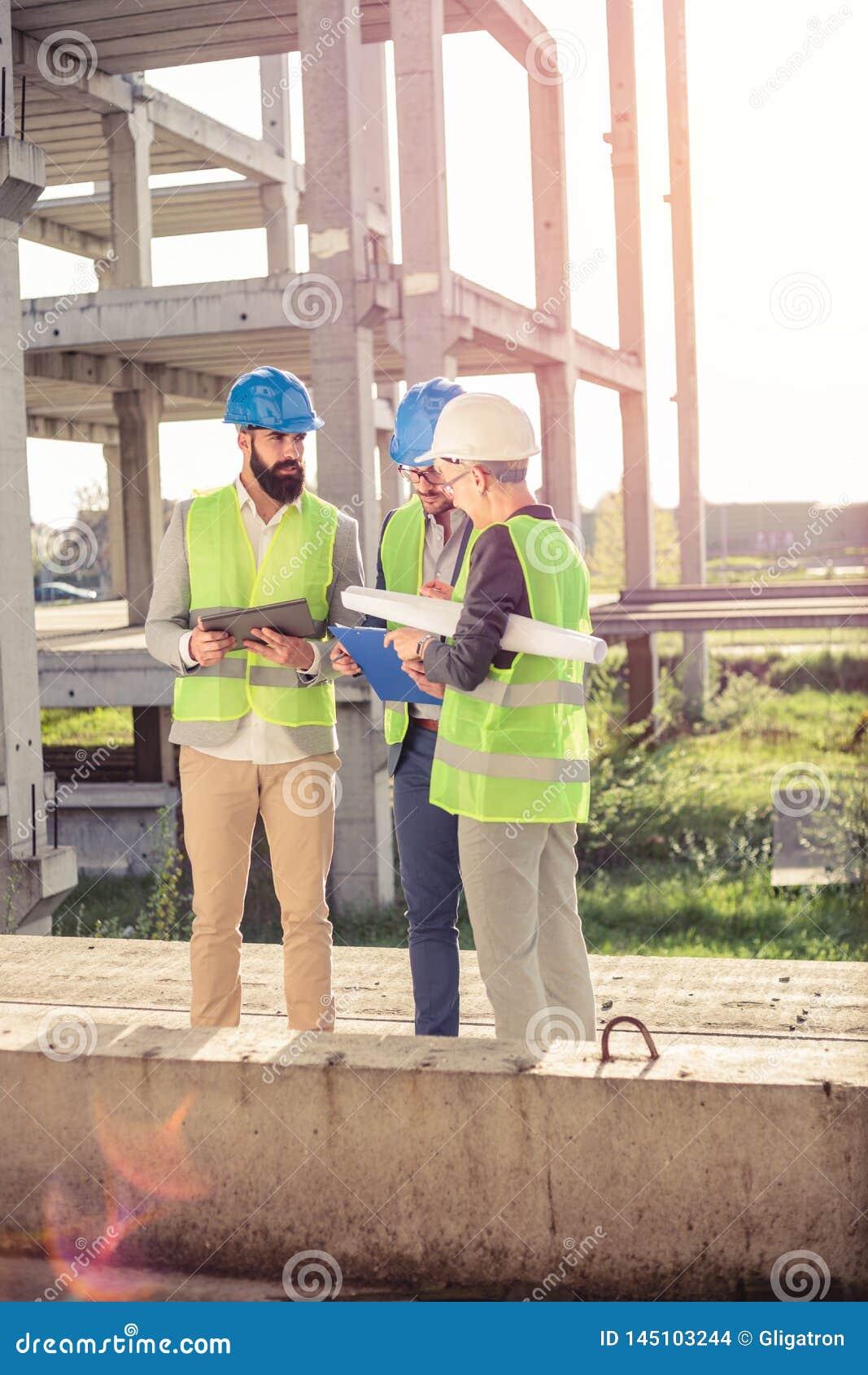 Kleine groep architecten en civiels-ingenieur die op een bouwwerf samenkomen