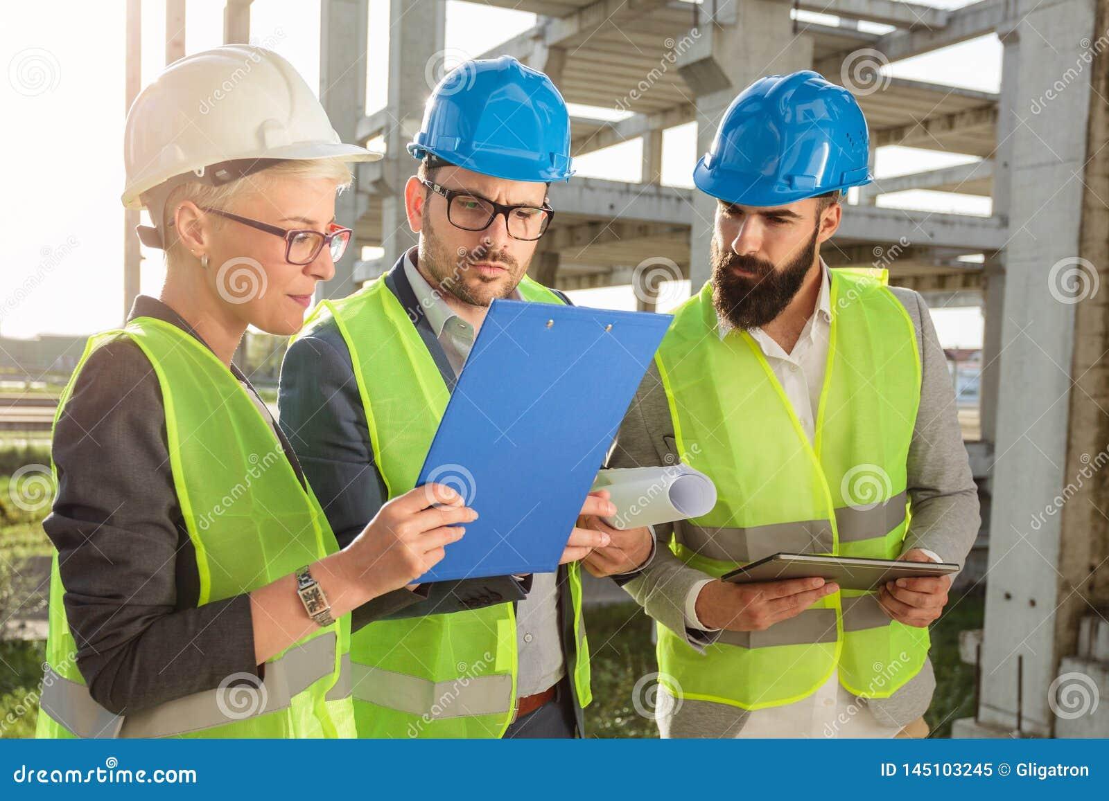 Kleine groep architecten en civiels-ingenieur die toekomstige plannen bespreken en projectdocumentatie bekijken