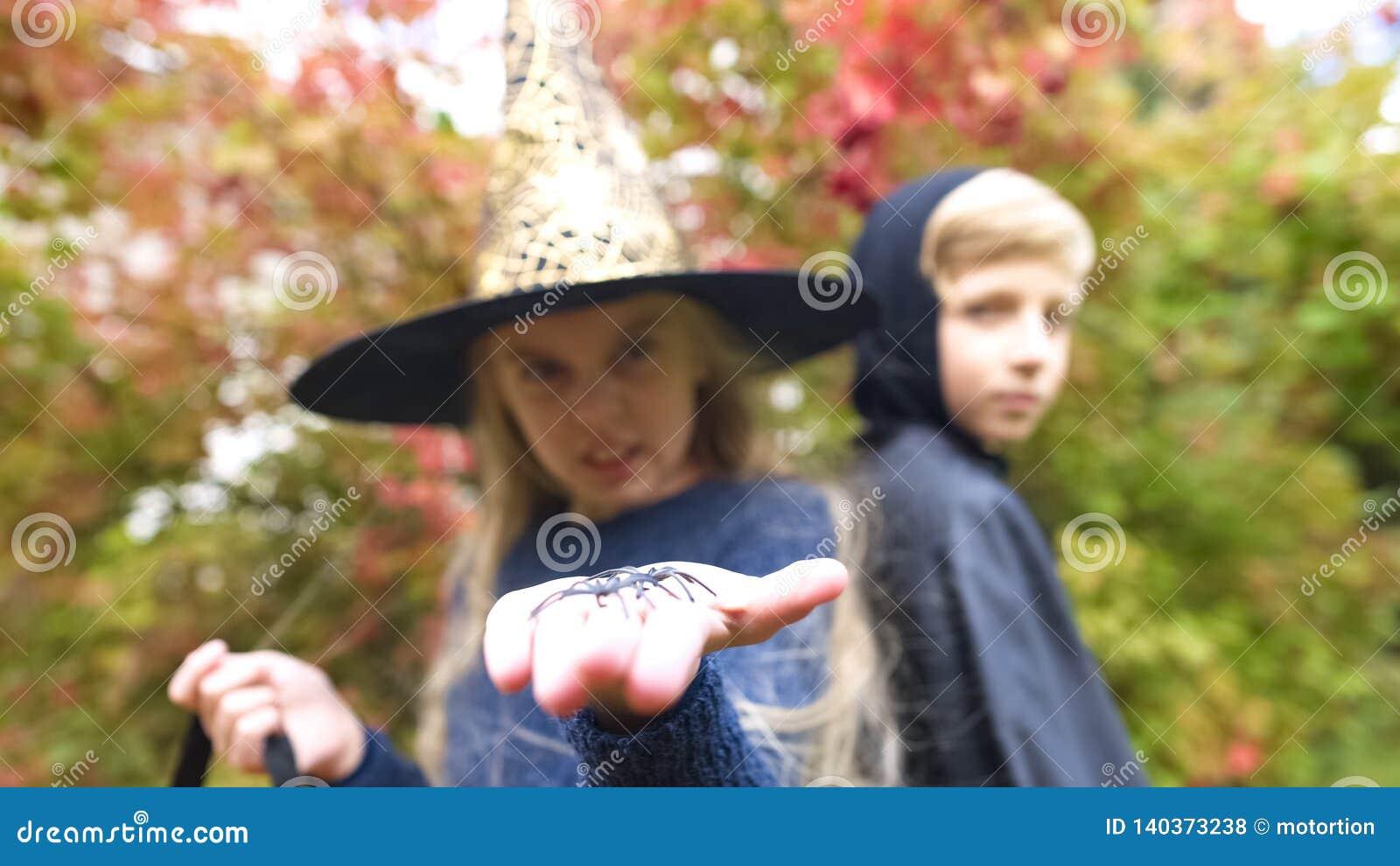 Kleine Hexe, die Spielzeugspinne in Kamera, arachnophobia, Furcht auf Halloween zeigt
