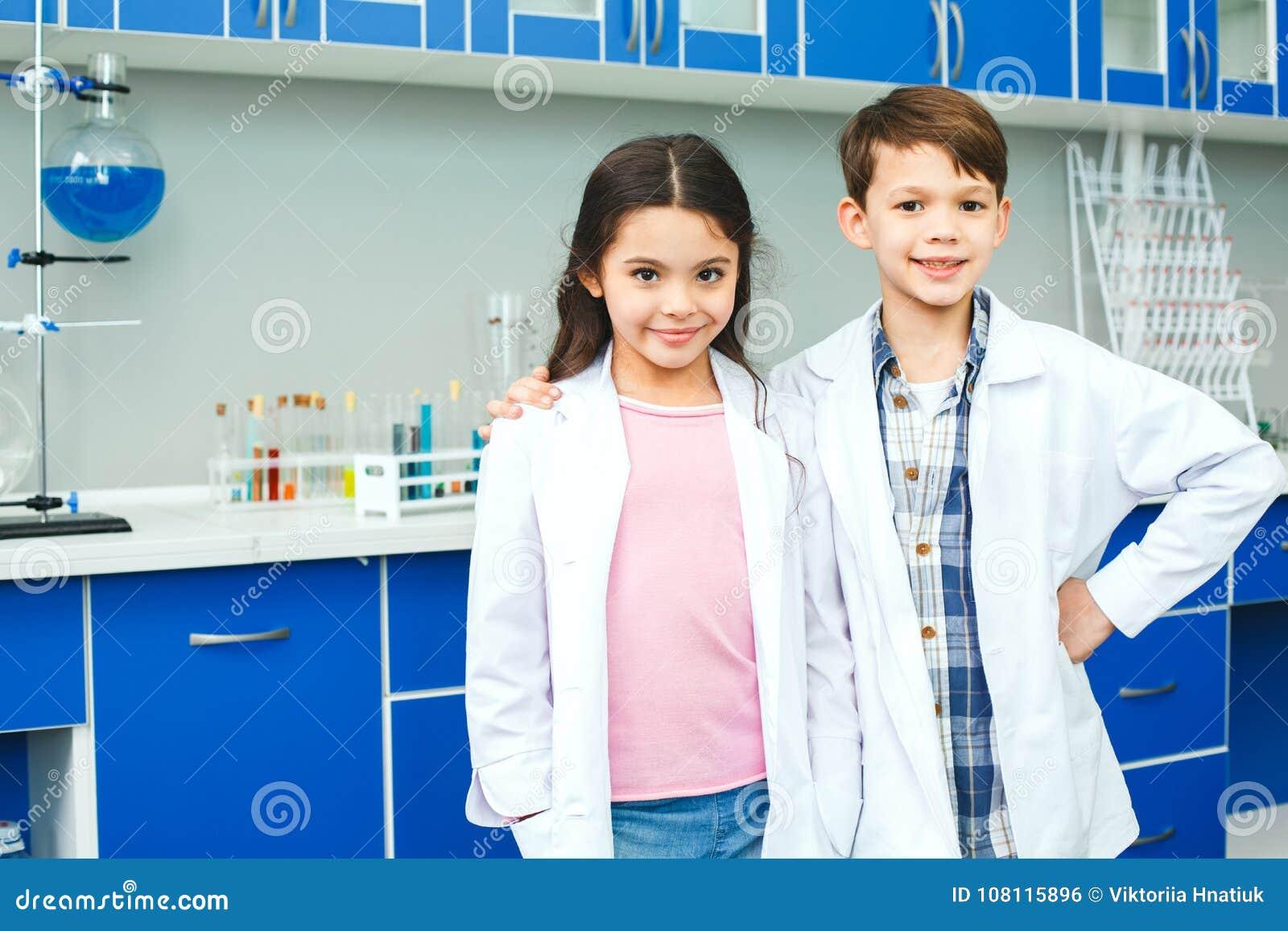 Kleine jonge geitjes die chemie in de beste vrienden van het schoollaboratorium leren