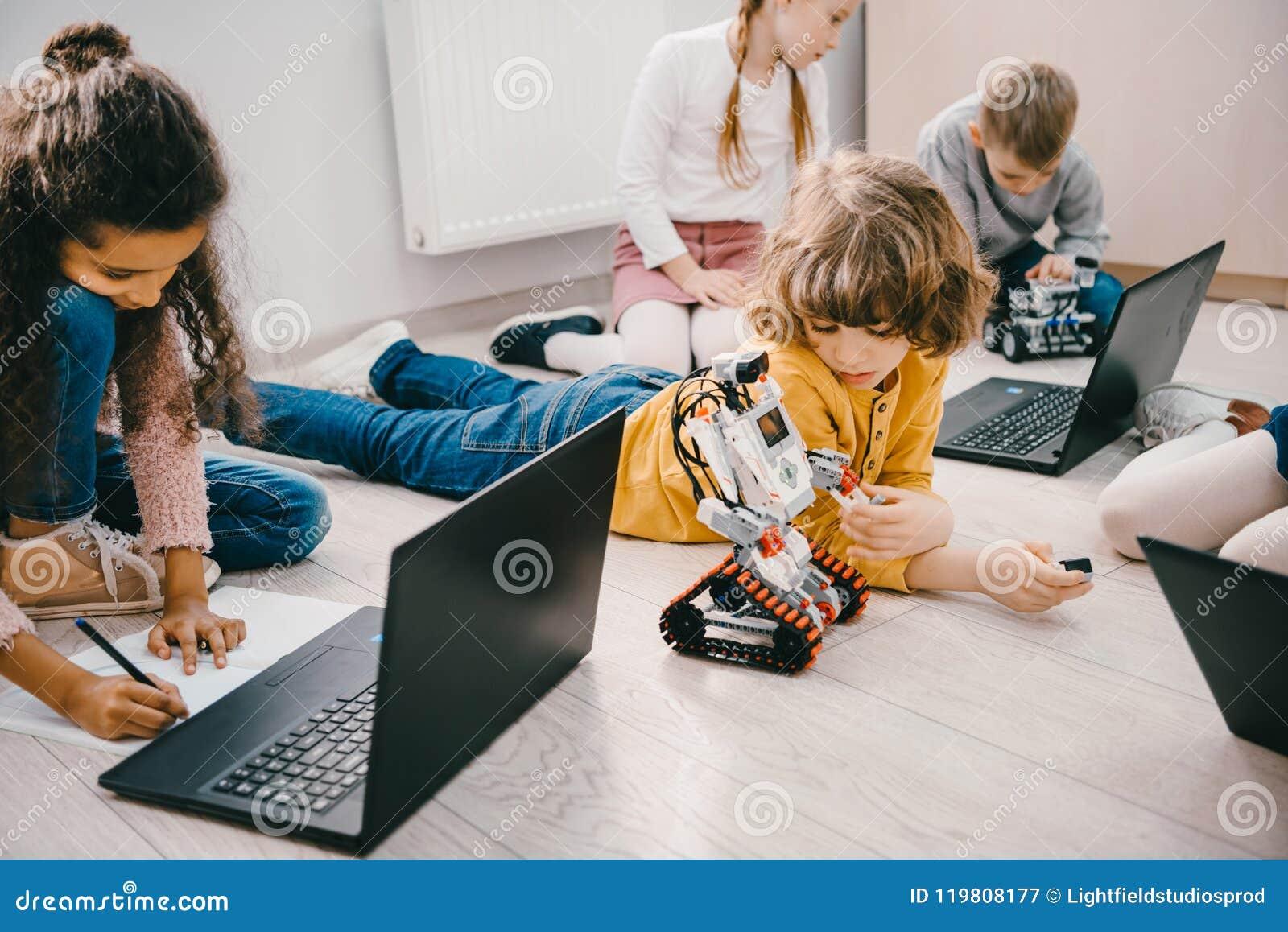 Kleine jonge geitjes die met laptops programmeren terwijl het zitten op vloer, stam