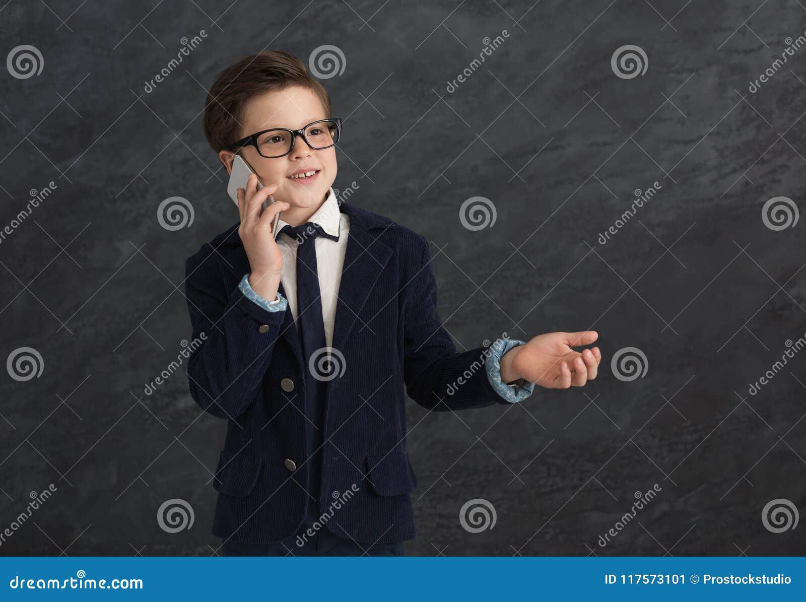 Kleine jongen in kostuum die op mobiel bij grijze achtergrond spreken
