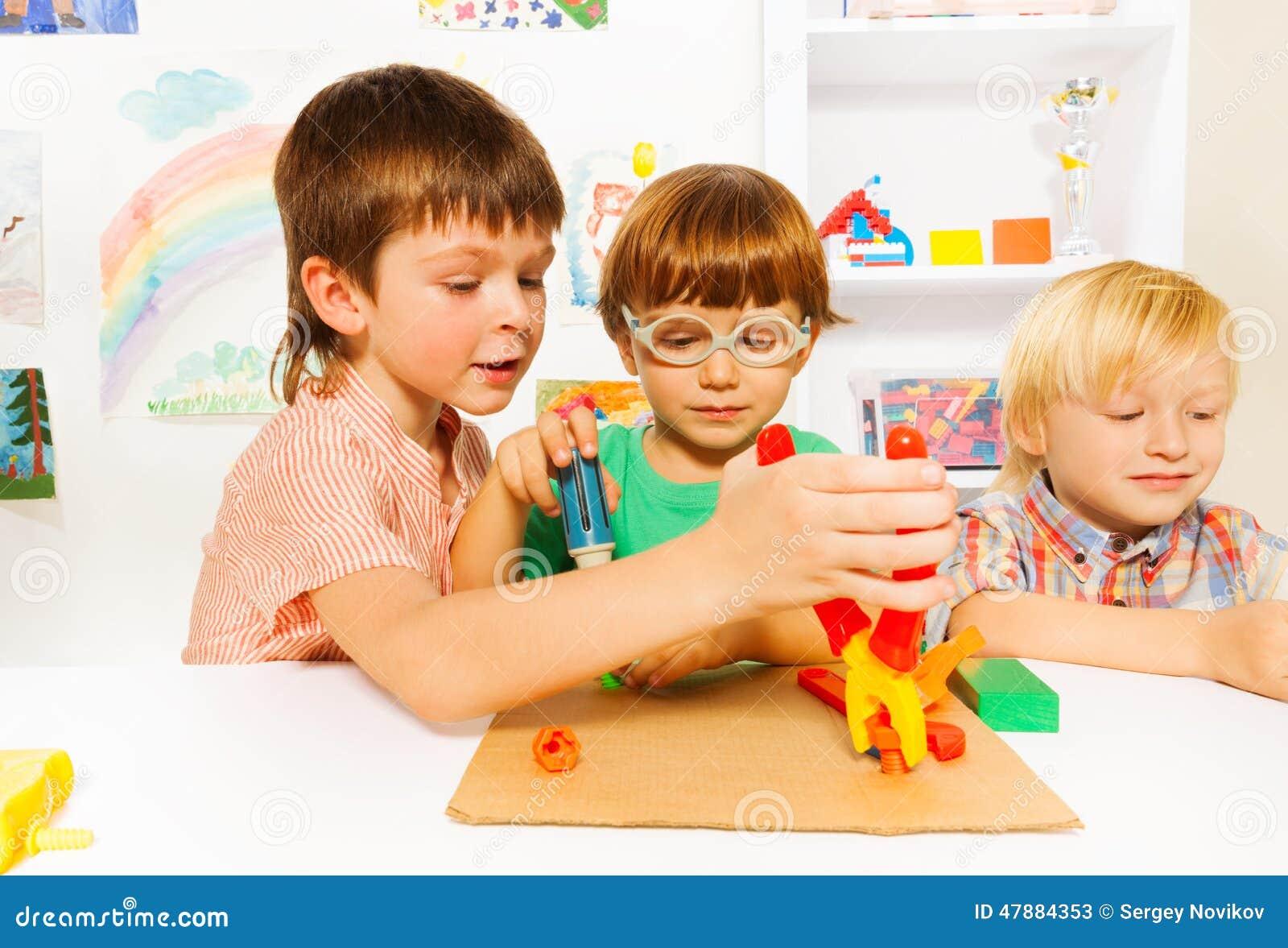 Kleine jongens met stuk speelgoed buigtang in klaslokaal