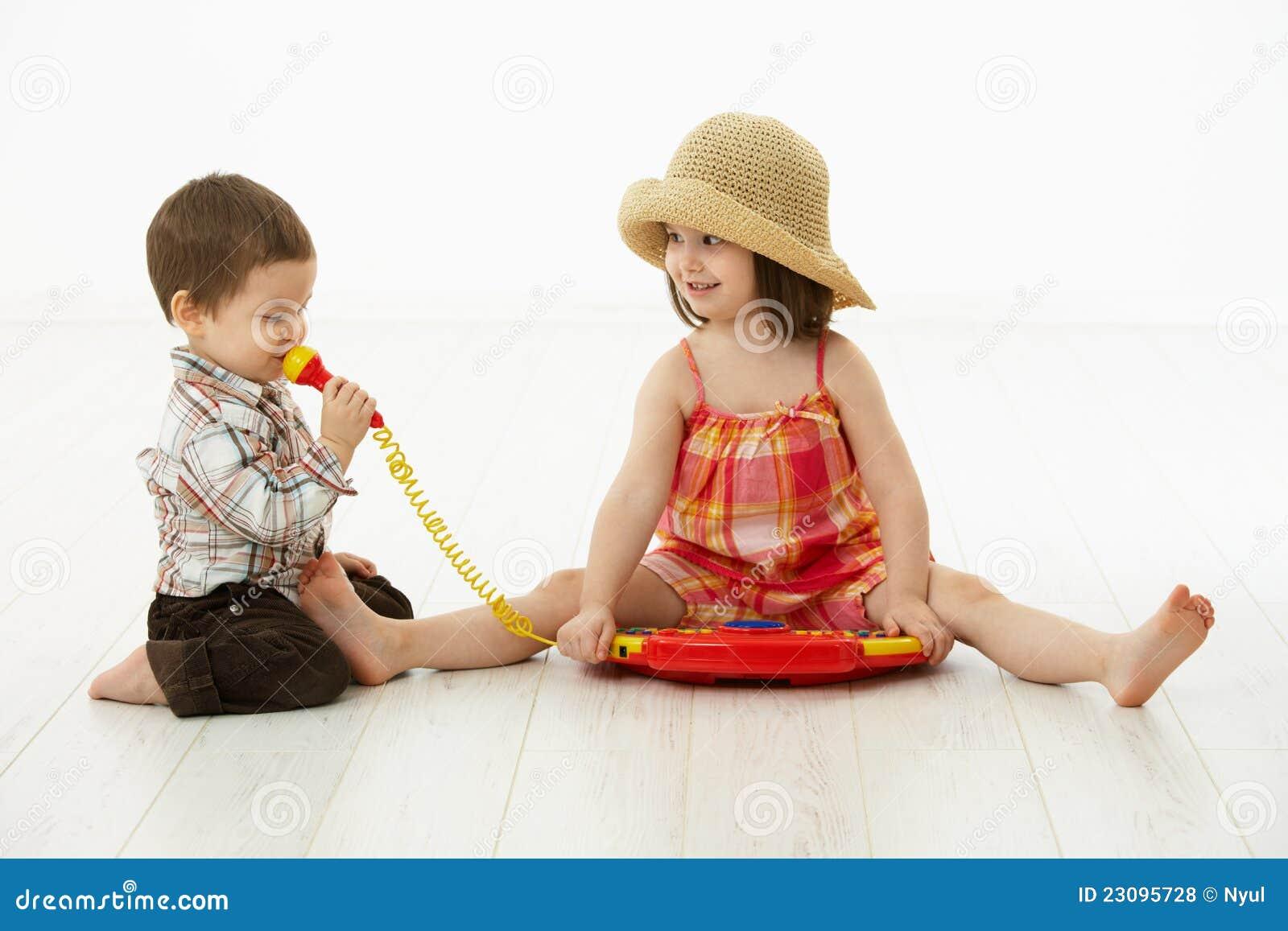 Kleine Kinder, die mit Spielzeuginstrument spielen