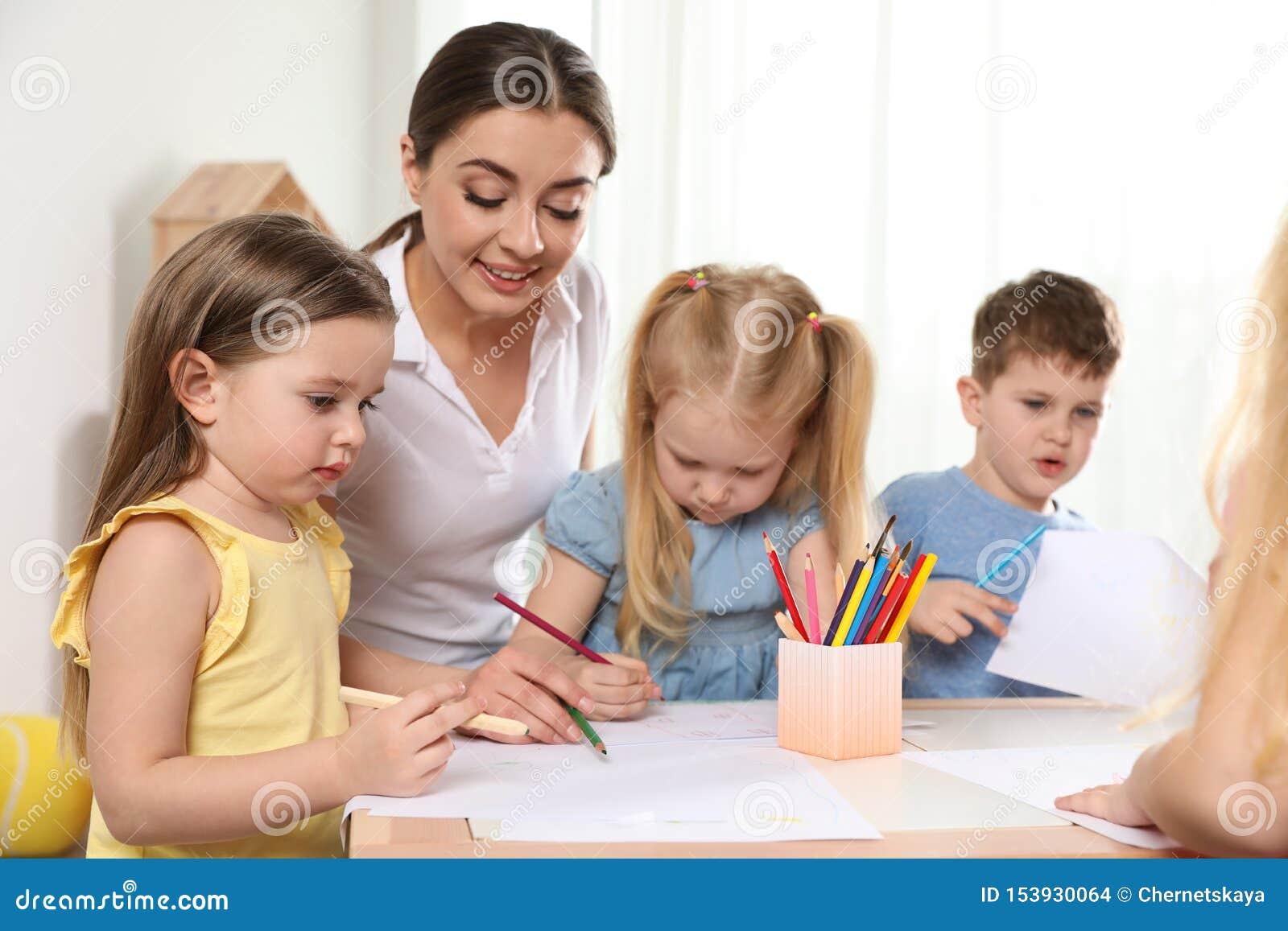 Kleine kinderen met de tekening van de kleuterschoolleraar bij lijst Het leren en het spelen