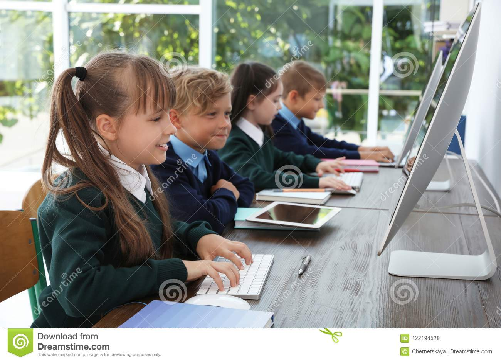 Kleine kinderen in modieuze school eenvormig bij bureaus