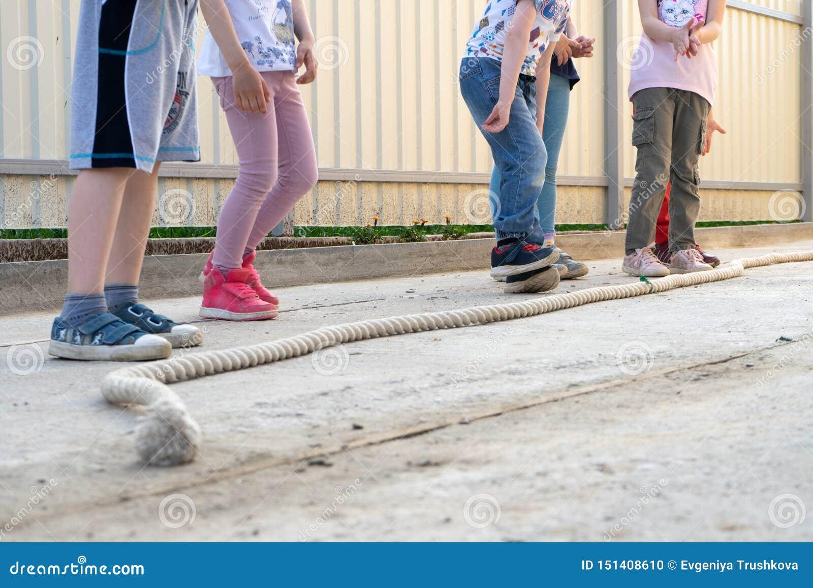 Kleine kinderenjongens en meisjes die spelen spelen - spring over de kabel die klaar te springen worden Perspectief op de benen