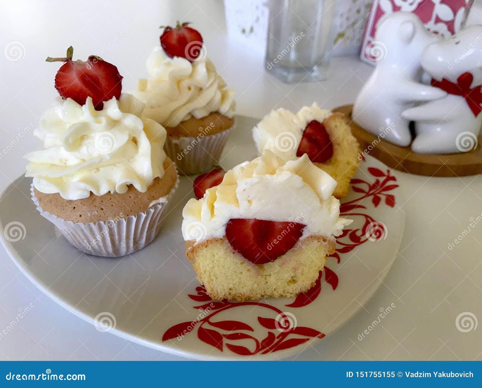 Kleine Kuchen mit Erdbeeren und Buttercreme Eins von ihnen wird geschnitten, die Füllung ist sichtbar Auf einer weißen Oberfläche