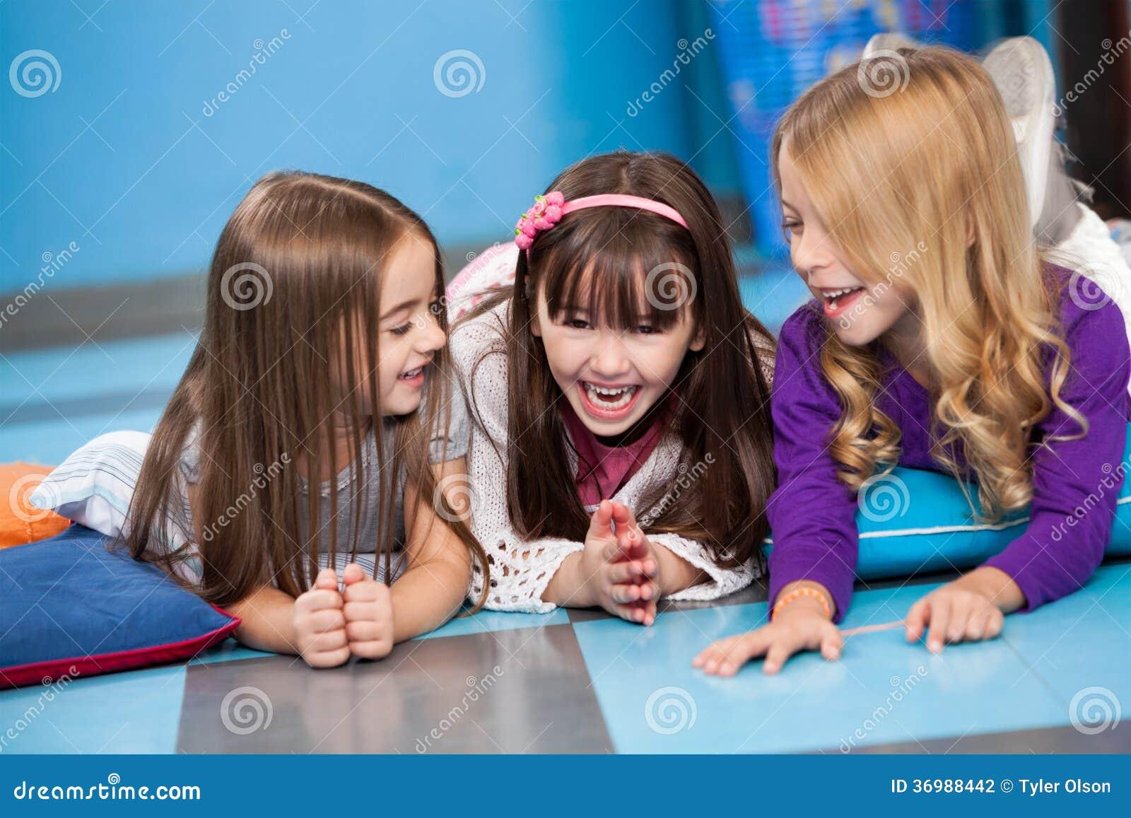 Kleine lachende Mädchen beim Lügen auf Boden