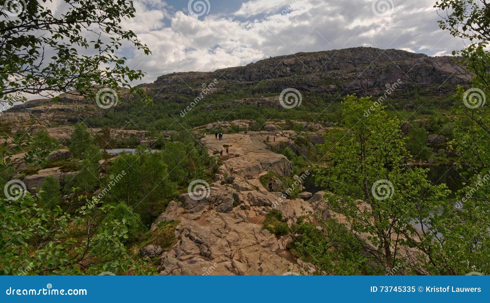 Kleine Leute, die auf einem großen Bergplateau in Rogaland, Norwegen wandern