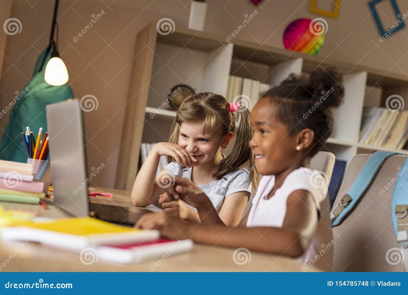Kleine M?dchen, die Karikaturen auf Laptop-Computer aufpassen