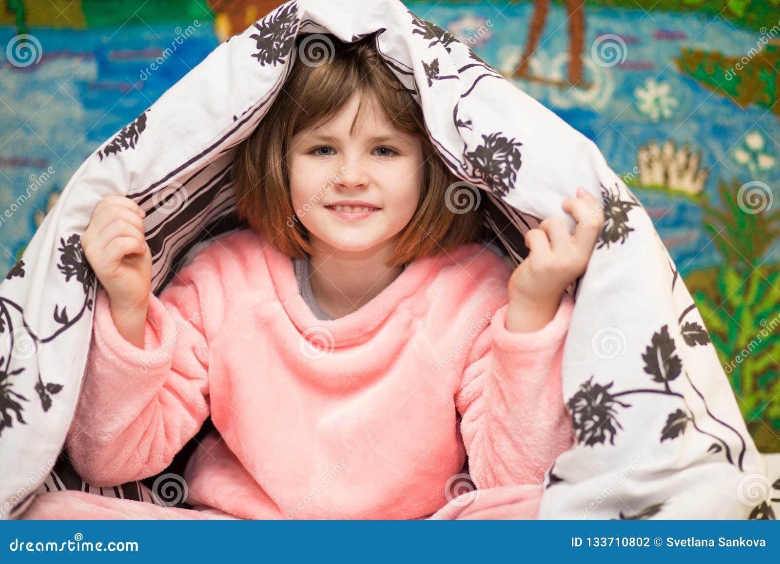 Kleine nette Mädchenfelle unter Decke Süßes Mädchen, das Spaß auf Bett hat Konzept des Kinderschlafes