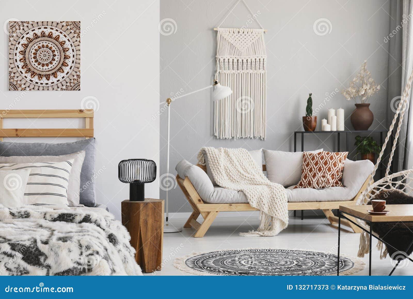 Kleine open plek vlak binnenlands met beige bank met kussen, macramé op de muur, rek met kaarsen en installaties en bed met