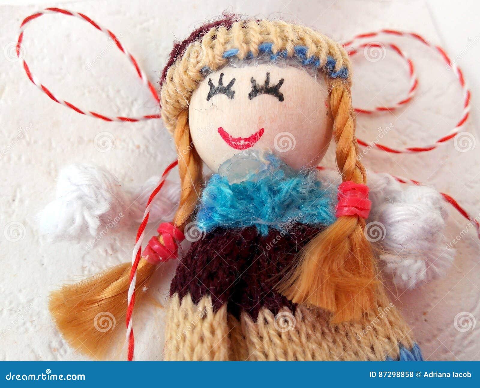 Kleine pop met rood en wit koord