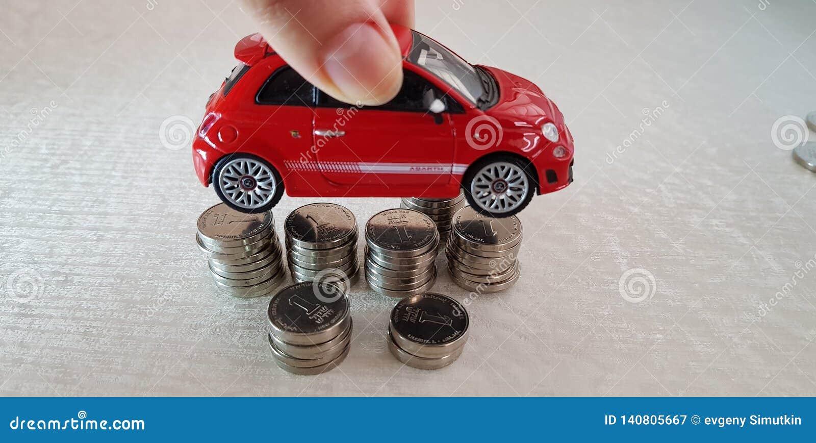 Kleine rode toestemming 500 stuk speelgoed in haar stapel van Israëlische sjekelmuntstukken overhandigen schikte op een andere in