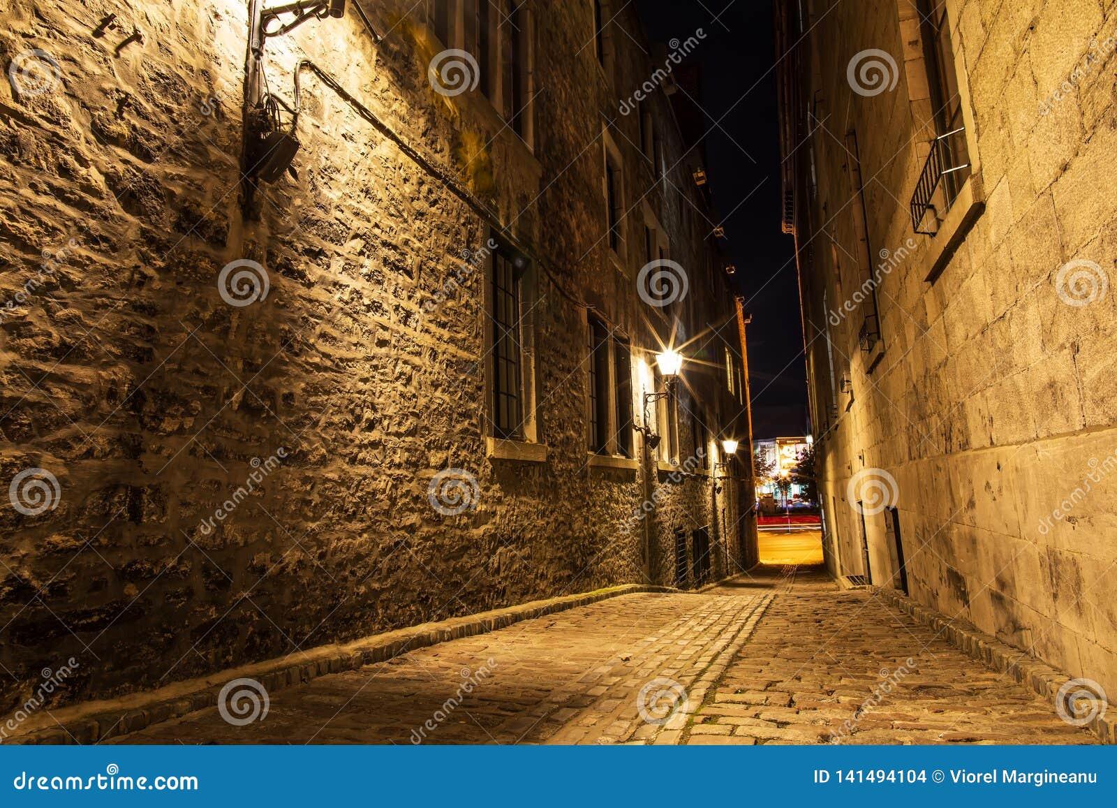 Kleine Straße und historische Gebäude in der historischen Stätte des alten Hafens von Montreal, Nachtansicht Szenischer Hintergru