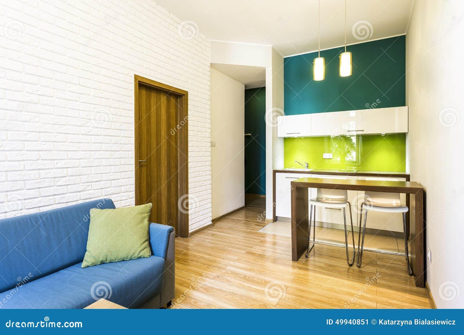 Kleine woonkamer met groene kitchenette stock afbeelding