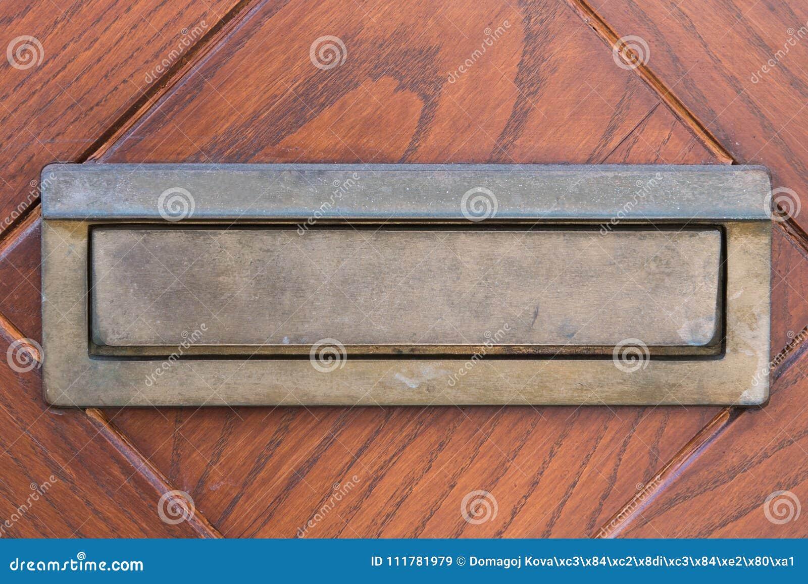 Kleine zilveren deurbrievenbus op houten deuren Kleine lettervakje