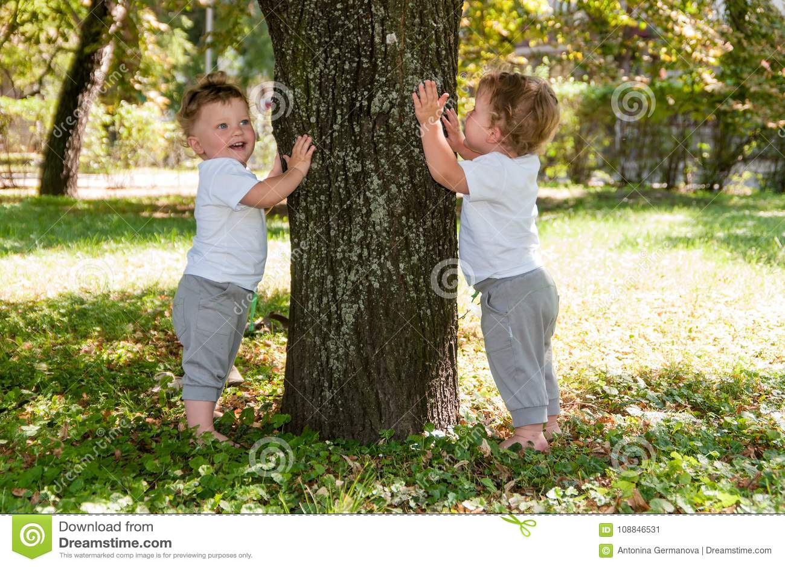 Kleine Zwillinge, gelockte Jungen in den weißen T-Shirts, einen Baum umarmend